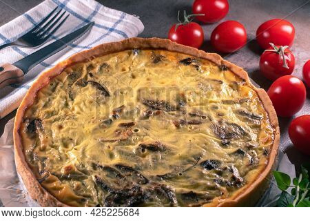 Closeup Of A Freshly Baked Yellow Quiche With Mushrooms Still On A Baking Paper, Sitting On A Dark K