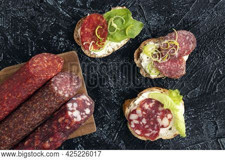 Flat Lay Three Kinds Of Different Sausages And Three Sandwiches Or Snacks With Them On A Black Textu