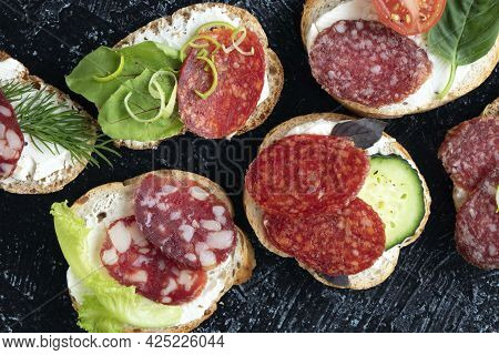 Close-up Kinds Sandwiches Or Snacks With Different Kind Of Sausages And Vegetables On A Black Textur