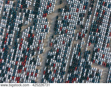 Many Thousands Of New Passenger Cars Are Standing In Straight Rows In A Giant Parking Lot On The Ter