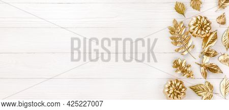 Gold Autumn Leaves On White Wooden Background. Autumn Concept. Top View Of Autumn Leaves In Gold Pai