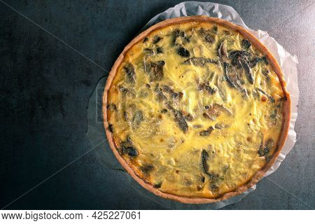 Top View Of A Freshly Baked Yellow Quiche With Mushrooms Still On A Baking Paper, Sitting On A Dark