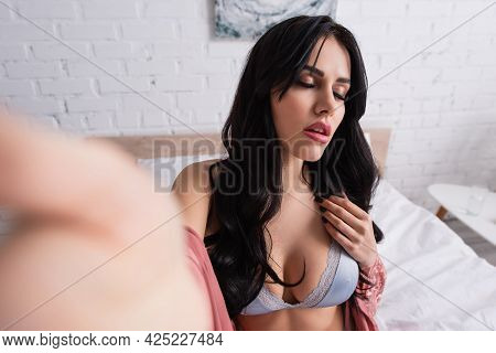Passionate Young Woman With Closed Eyes In Bra And Silk Robe In Bedroom