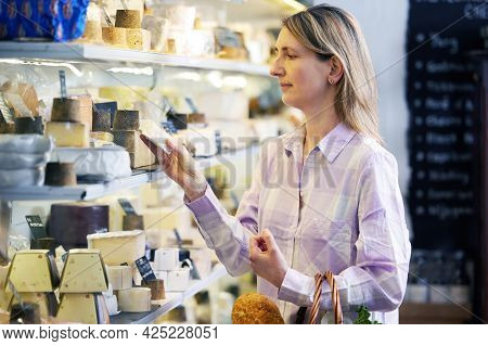 Female Customer Shopping For Local Cheese In Delicatessen Food Shop