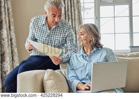 Smiling Mature Couple At Home Reviewing Domestic Finances On Laptop
