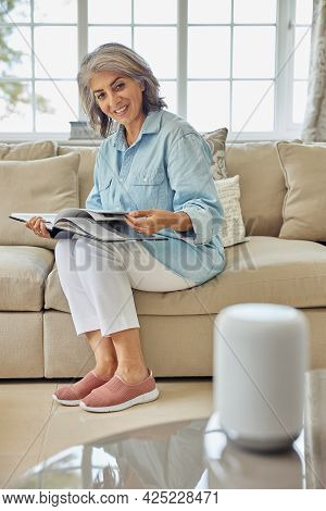 Mature Woman Sitting On Sofa Asking Digital Assistant Or Smart Speaker Question