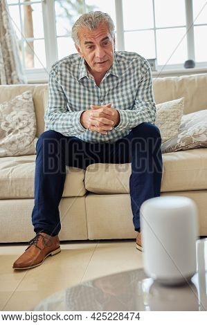 Mature Man Sitting On Sofa Asking Digital Assistant Or Smart Speaker Question