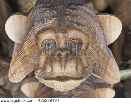 Russia, Sochi 06.06.2021. The Muzzle Of A Wooden Figurine Of A Monkey Covering The Ears With His Han