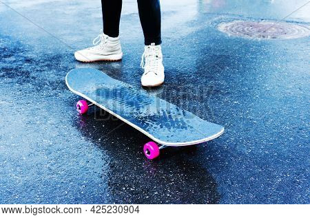 Skateboarding Skateboard With Pink Wheels And Legs Of A Novice Skateboarder In White Sneakers On Wet