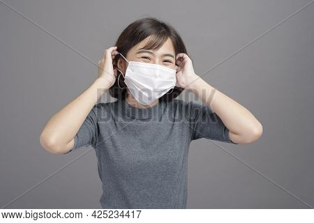 A Portrait Of Young Beautiful Asian Woman Wearing A Surgical Mask Over Studio Background, Covid19 Pa