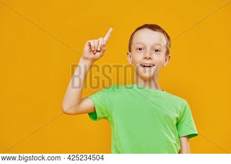 Funny cheerful boy smiles and attracts attention with his forefinger. Children and education. Studio portrait on a yellow background with copy space.