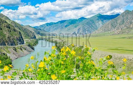 View Of A Picturesque River Valley Among High Mountains With A Winding Highway Near The Edge Of A Cl