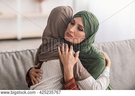 Senior Muslim Mother Hugging Unhappy Adult Daughter Wearing Hijab Indoor