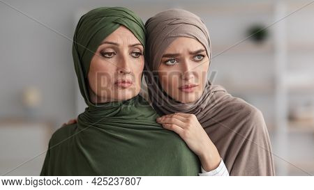 Unhappy Senior Muslim Lady And Her Adult Daughter Embracing Indoor