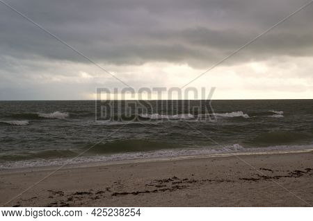 Thick Heavy Storm Clouds Fill The Sky Over The Gulf Of Mexico In Bonita Springs, Florida, As Waves C