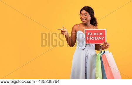 Charming Black Woman With Shopper Bags Holding Black Friday Sign And Pointing Aside At Empty Space,