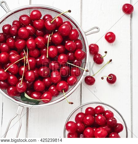 Fresh Cherries On A White Wooden Background.