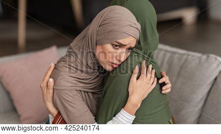 Unhappy Muslim Woman Hugging Depressed Senior Mother At Home, Panorama