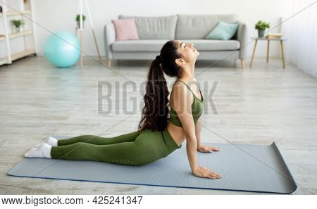 Side View Of Indian Woman Doing Yoga Cobra Pose Or Pilates On Mat In Living Room. Stay Home Hobbies