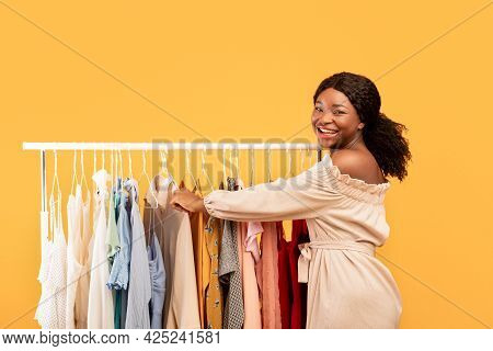 Seasonal Shopping Concept. Black Female Choosing Clothes From Rack, Following Latest Fashion Trends