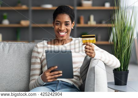 Smiling Black Woman Using Digital Tablet And Credit Card For Online Shopping