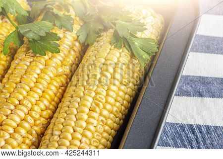 Home Cooking Recipe Baked Corn With Salt, Butter And Cilantro Or Parsley In Foil. Homemade Food Conc