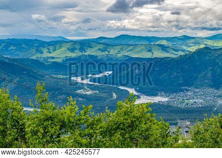 View From The Top Of The Mountain To A Huge Valley With A Winding River In Cloudy, Rainy Weather Wit