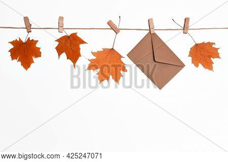 Autumn Leaves Background, Fallen Maple Leaves Hanging On Clothespins On A Rope With Craft Envelope,