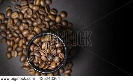 Ceramic Cup With Coffee Beans On A Blurred Background From Coffee Beans Scattered On A Dark, Top Vie