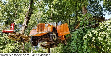 Klaipeda, Lithuania - Juny 24, 2021: Orange Retro Car Is Hanged On The Tree. Central Public Park Of