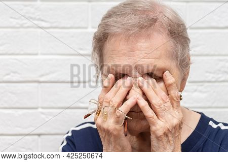 Close Up Of Unhealthy Elderly Woman Take Off Glasses Massage Eyes Suffering From Strong Migraine Or