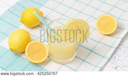 Lemon Juice In The Glass With Blue Drinking Straws And Fresh Lemons At The Background On The Light B