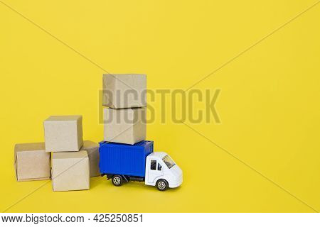 Carton Boxes And Blue Cargo Truck On Yellow Background. Cargo Transportation, Delivery Service. Tran