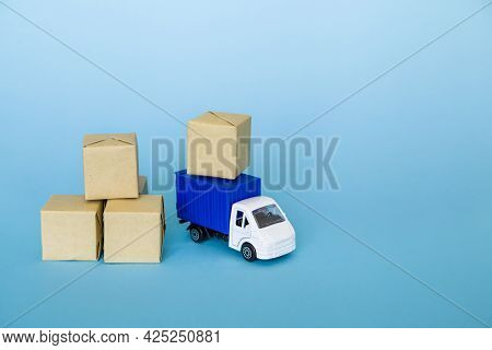 Carton Boxes And Blue Cargo Truck On Blue Background. Cargo Transportation, Delivery Service. Transp