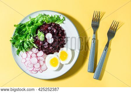 A Dietary Dish Made From Vegetables. Beet Tartare, Radish, Frieze Salad And Boiled Egg On A Plate An