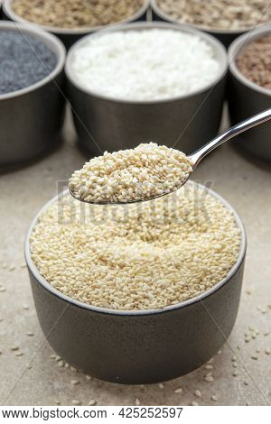 White Sesame Seeds, Sesame Seeds In A Black Saucer On A Background Of Various Seeds. Male Hand Sprin