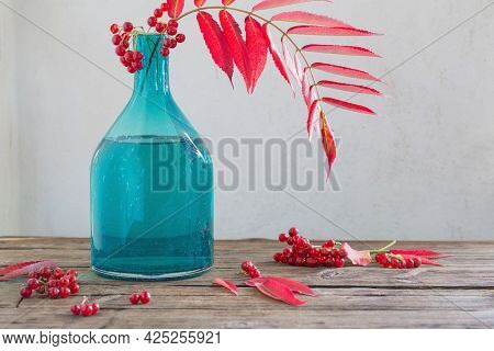 Red Autumn Leaves In Glass Vase And Viburnum Berries  On Wooden Table