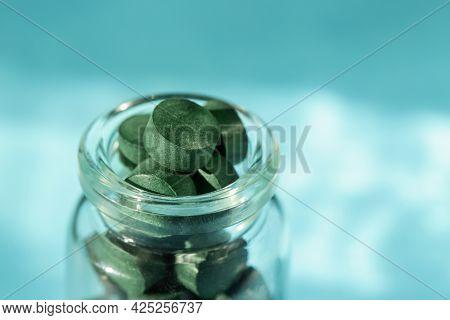 Spirulina Pills In Glass Bottle On Blue Background. Antioxidant Nutrition. Copy Space