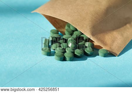 Green Spirulina Tablets With Eco Bag On Blue Background. Natural Superfood, Vegan, Healthy Dietary S