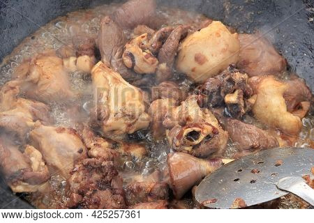 Large Pieces Of Lamb Meat With Lamb Fat Dumba Close-up Fried In Oil With Bubbles In A Black Cauldron