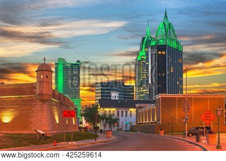 Mobile, Alabama, USA downtown skyline with Fort Conde's corner turret at dusk.