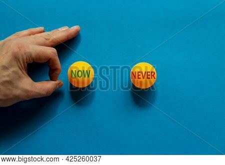 Now Or Never Symbol. Male Hand Is About To Flick The Ball. Orange Table Tennis Balls With Words Now