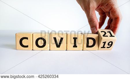 Symbol Of Covid-19 Pandemic In 2021 Year. Businessman Turns The Wooden Cube And Changes Words 'covid