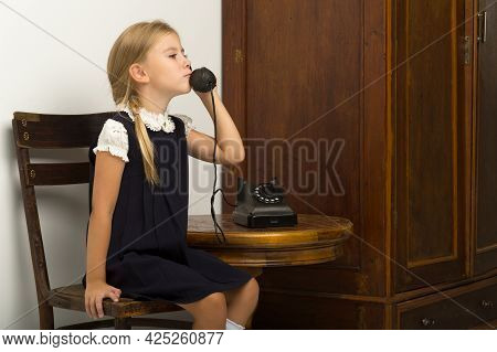 A Cute Girl Is Talking On An Old Phone. A Lovely Blonde Talking On An Old-fashioned Phone In The Stu