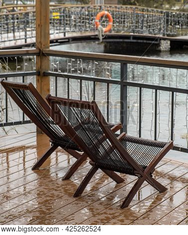 Two Chairs On A Wet Terrace In The Rain. Terrace With A Pond In Autumn.