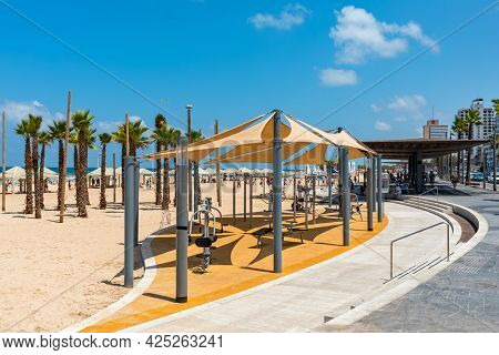 TEL AVIV, ISRAEL - JULY 19, 2017: Promenade along public beach with open air gym on the sand in Tel Aviv -  economic and technological center, second most populous city of Israel.