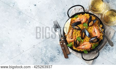 Traditional Spanish Seafood Paella In Pan With Chickpeas, Shrimps, Mussels, Squid On Light Grey Conc
