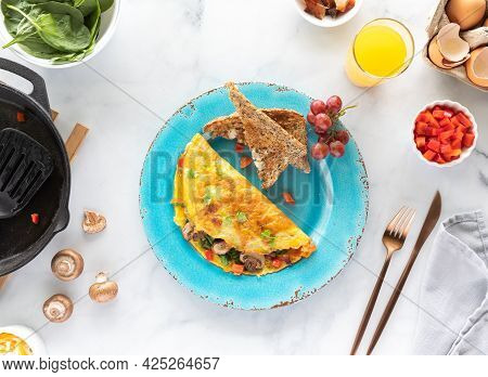 Top Down View Of A Plate With A Freshly Made Omelette Served With Toast And Orange Juice.