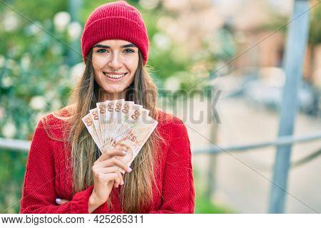 Young hispanic woman wearing wool cap holding turkish lira banknotes at the city.