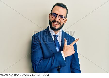 Young man with beard wearing business suit and tie cheerful with a smile of face pointing with hand and finger up to the side with happy and natural expression on face